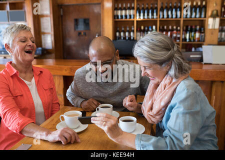 Happy friends looking their photos on mobile phone in bar - Stock Photo