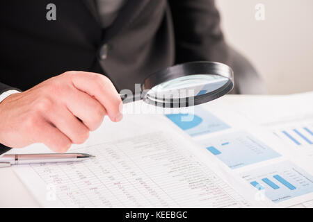 Businessman reading documents with magnifying glass concept for analyzing a finance - Stock Photo
