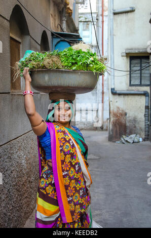 AHMEDABAD, INDIA - NOVEMBER 27, 2016: Female Vegetable Vendor wearing traditional saree in the street of Ahmedabad - Stock Photo