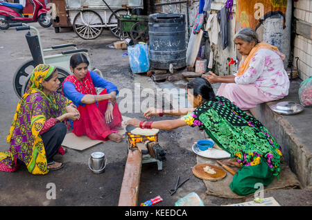AHMEDABAD, INDIA - NOVEMBER 27, 2016: Muslim women cooking chapatti and food for family on the side of the street - Stock Photo