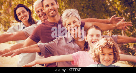 Portrait of extended family smiling in park - Stock Photo