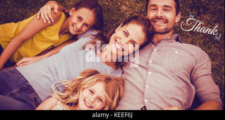 Digital image of happy thanksgiving day text greeting against portrait of happy family lying on field - Stock Photo