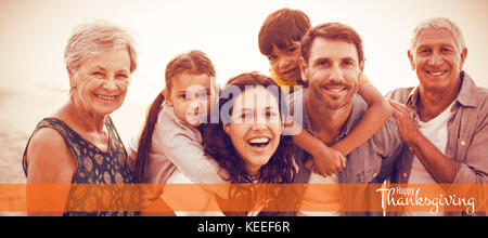 Illustration of happy thanksgiving day text greeting against happy family posing at beach - Stock Photo