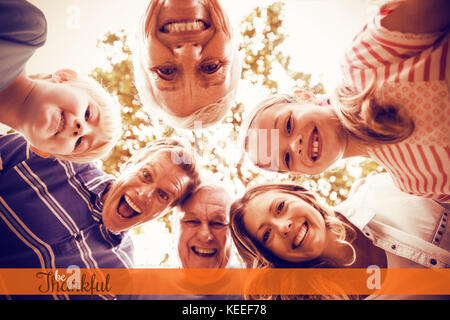 Thanksgiving greeting text against portrait of happy multi-generation family forming a huddle in park - Stock Photo