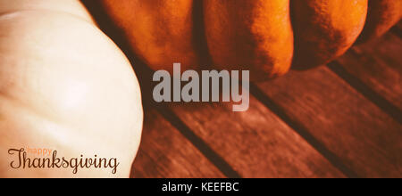 Digital generated image of thanksgiving greeting against close up of pumpkins on wooden table - Stock Photo