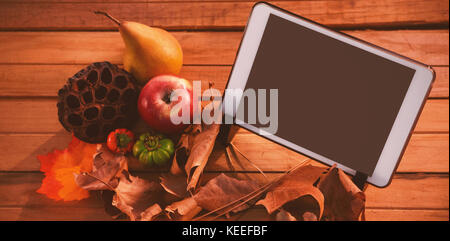 Touch pad on leaf on wood table surround of fruits - Stock Photo