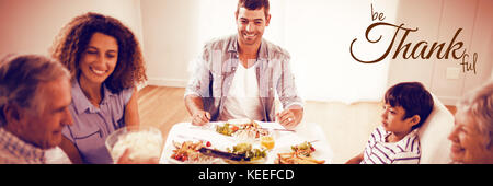 Digital image of happy thanksgiving day text greeting against happy family having breakfast together - Stock Photo