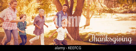 Digital generated image of thanksgiving greeting against happy family playing soccer - Stock Photo