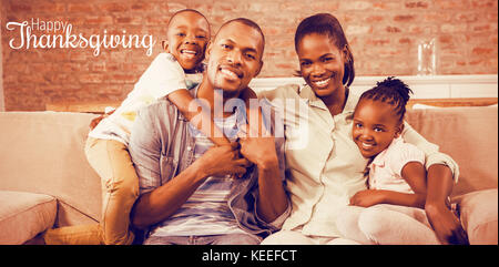 Thanksgiving greeting text against happy family relaxing on couch - Stock Photo