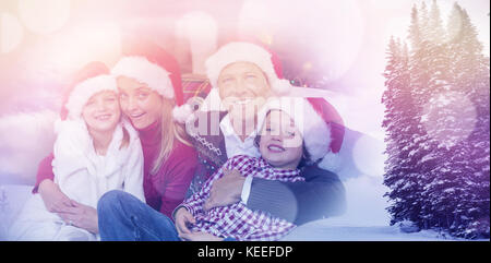 Scenic view of snow covered trees and mountain against festive family in santa hat hugging on couch - Stock Photo