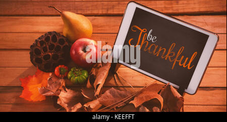Thanksgiving greeting text against touch pad on leaf on wood table - Stock Photo