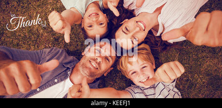 Digital image of happy thanksgiving day text greeting against happy family in park together gesturing thumbs up - Stock Photo