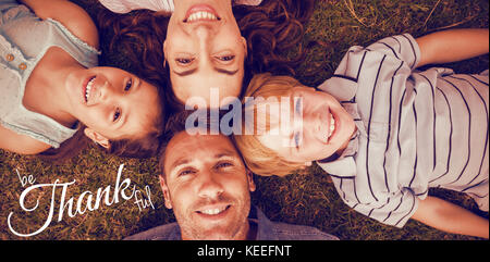 Digital image of happy thanksgiving day text greeting against happy family in park together - Stock Photo