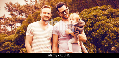 Happy gay couple with child in garden - Stock Photo