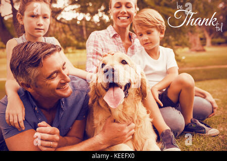 Digital image of happy thanksgiving day text greeting against happy family enjoying with dog at park - Stock Photo