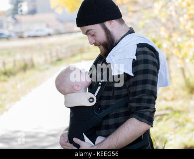 Millennial Dad with Baby in Carrier Outside Walking - Stock Photo