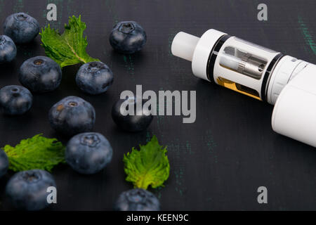 white electronic cigarette on a dark table, next to a scattered berry - Stock Photo