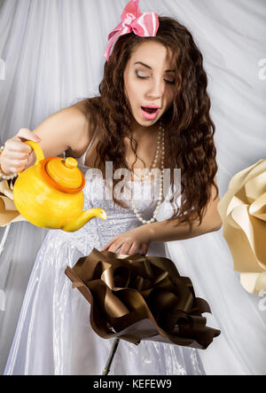 young woman dressed as Alice in Wonderland with big kettle and flowers - Stock Photo