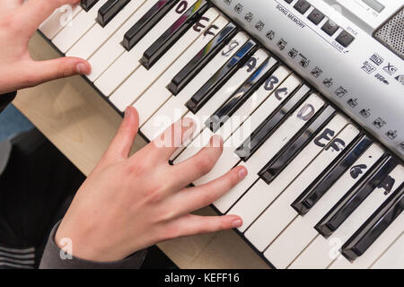 Pupil practising the keyboard in a UK state secondary school - Stock Photo