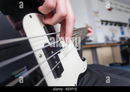 Pupil in a UK state school playing the bass guitar in music lesson - Stock Photo