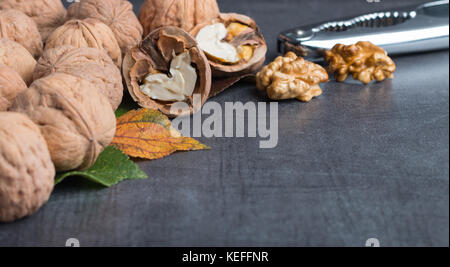 bio walnuts on a stone table with a nutcracker - Stock Photo