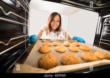 Young Happy Woman Baking Fresh Cookies In Oven At Kitchen - Stock Photo