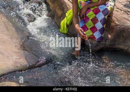 Woman in African outfit on the verge of fluent river. Interacting with water. Angola. - Stock Photo