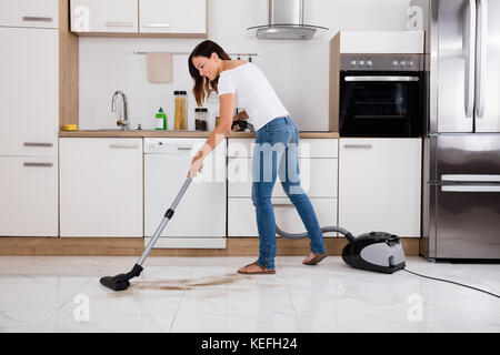 Young Happy Woman Cleaning The Floor Of The Kitchen Using Vacuum Cleaner - Stock Photo