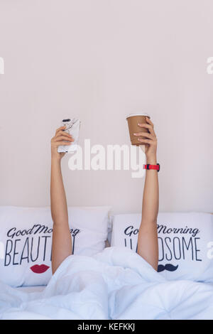 Womans hand holding a cup of coffee and a phone under blanket on the bed - Stock Photo
