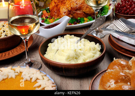 A bowl of mashed potatoes on a table among the pumpkin pie, baked turkey, cranberry-orange sauce,   a glass of white - Stock Photo