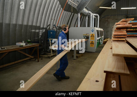 GREYMOUTH, NEW ZEALAND, 18 JULY, 2017: Workers use a four sider machine to plane rough edges from four sides of - Stock Photo