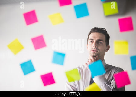 Portrait of young handsome start-up businessman leaning against wall with sticky notes and looking straight at camera - Stock Photo