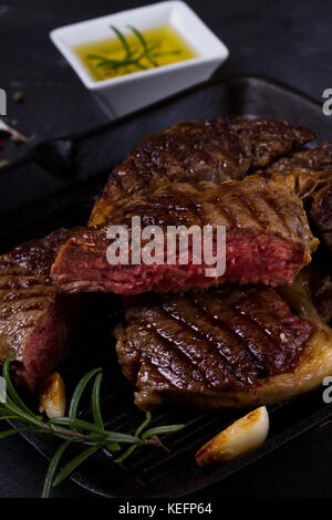 Grilled beef steak with spices on dark background - Stock Photo