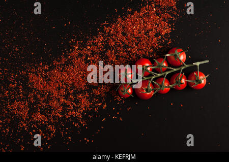 fresh tomatoes on a branch with crumbled red pepper closeup on a black background - Stock Photo