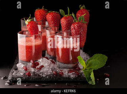 a few glasses of drink with strawberry and ice on a black stone on a dark background - Stock Photo