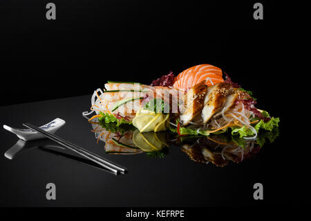 a set of sushi with shrimps and chopsticks on a black background with reflection - Stock Photo