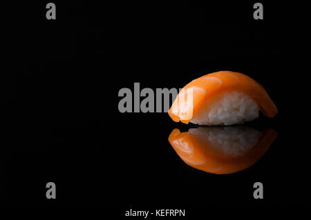 closeup of sushi with rice on black background with reflection - Stock Photo
