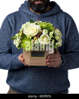 man holds white rose in a cardboard box. Valentine's Day - Stock Photo