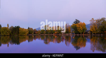 Autumn colors and reflection at the blue hour on the Puigcerda's pond water - Stock Photo
