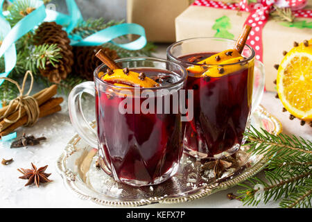 Homemade Christmas cocktail mulled wine red wine with cinnamon sticks, oranges and cloves, served in two cups on - Stock Photo