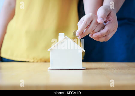 Close up shot hands of man and woman putting the coin to house piggy bank ratio metaphor and concept for Couple - Stock Photo