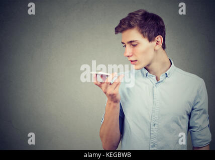 Young man using a smart phone voice recognition function isolated on gray wall background - Stock Photo