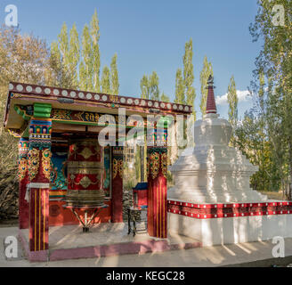 A prayer wheel and stupa in Ladakh, India - Stock Photo