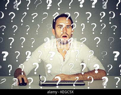 Amazed perplexed man working on desktop computer has many questions - Stock Photo