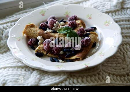 Pancakes with raspberries on a flower motive porcelain plate - Stock Photo