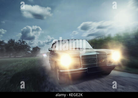Old-timer in full speed during night time - Stock Photo