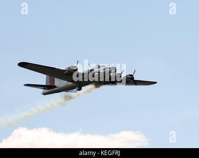 World War II era Flying Fortress bomber with smoke trail - Stock Photo