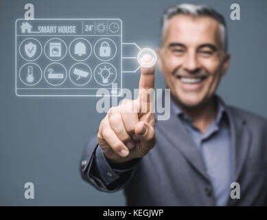 Confident man monitoring his smart house using a virtual touch screen interface system, home automation concept - Stock Photo
