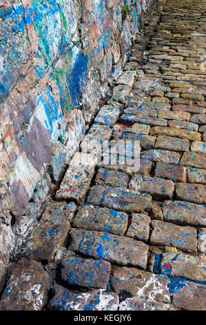 Abstract paint colour splashes where boats painted by sea wall in harbour of Castro Urdiales, Cantabria, Spain