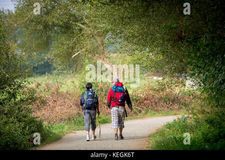 Pilgrim couple on the Camino de Santiago PIlgrim's Way to Santiago de Compostela in Galicia, Spain - Stock Photo